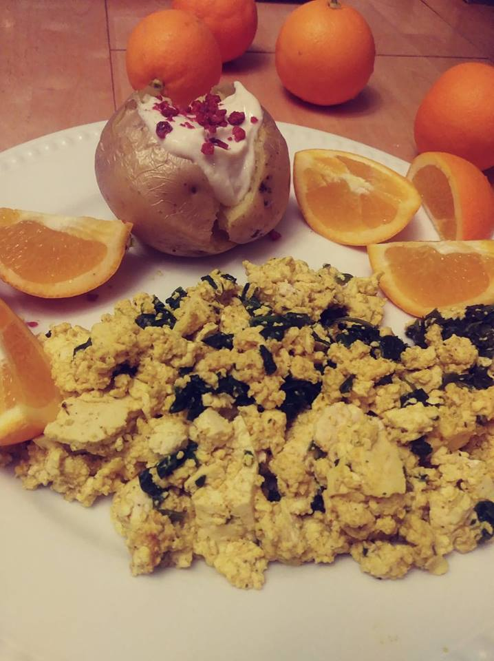 Scrambled tofu, otange slices and a baked potato with tofu sour cream and soy bacon bits