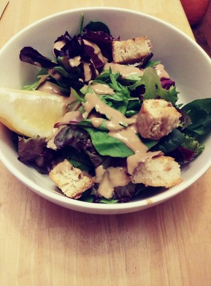 Caesar salad in a bowl with croutons and lemon wedges