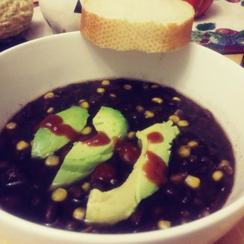 bowl of vegan black bean soup with avocado slices