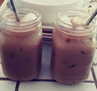 two mason jar cups with iced coffee and straws