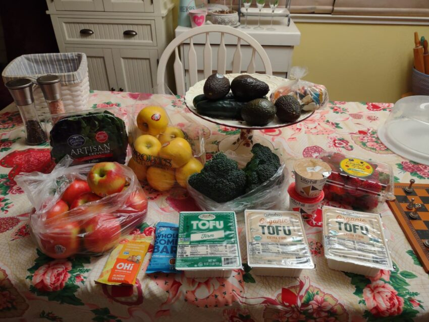 Sprouts Shopping Trip March 2021 laid out on my dining table. Includes apples, tofu, avocados, cucumbers, lettuce, strawberries, vegan unicorn gummies, broccoli,OHI Bars, Kite Hill Yogurt Cups