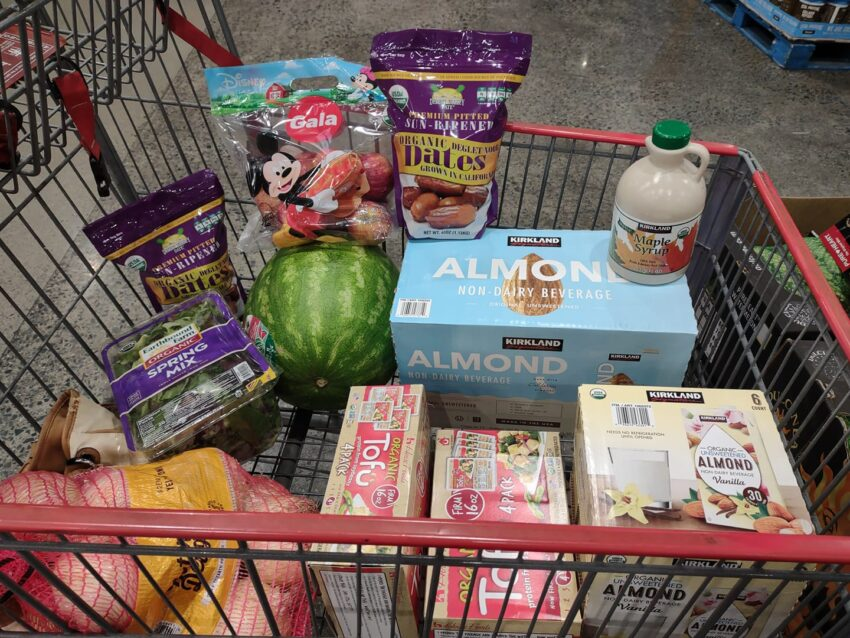 My cart at Costco with tofu, dates, watermelon, unsweetened almond milk and vanilla almond milk, salad pack, maple syrup, onions, apples