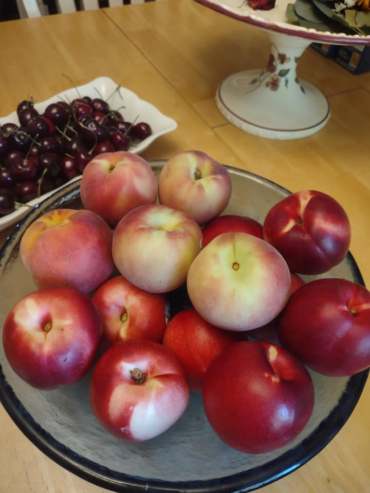 Nectarines and peaches in a bowl, cherries on a tray