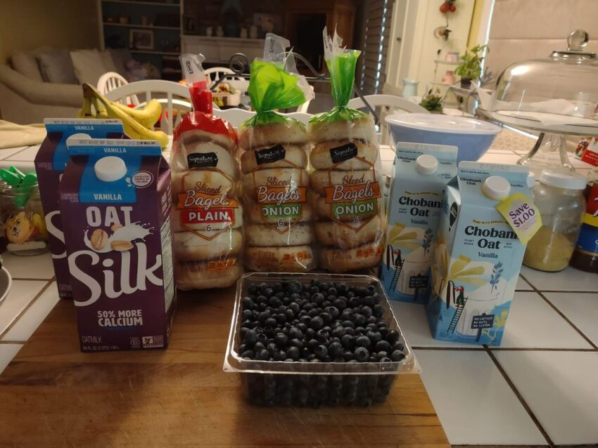 Three packs of Safeway bagels, Silk and Chobani Oatmilk and blueberries