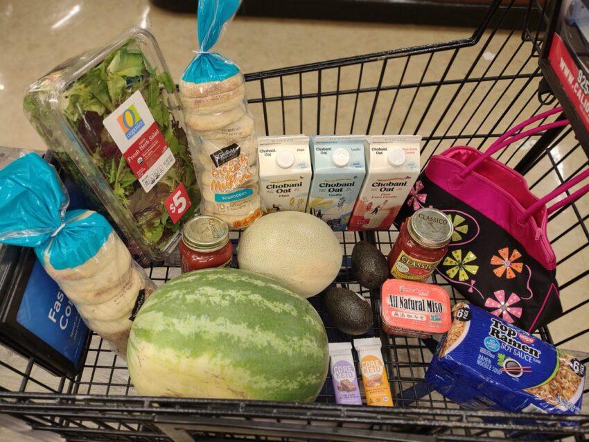 My cart full of vegan groceries, includes watermelon, cantaloupe, Chobani Oatmilk, Core Keto Bars, sourdough English Muffins, Classico pasta sauce, salad pack, soy sauce Top Ramen, avocados