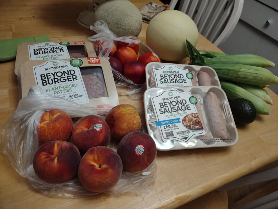 Packs of Beyond sausages and burgers, corn on the cob, peaches, cantaloupe and honeydew melons