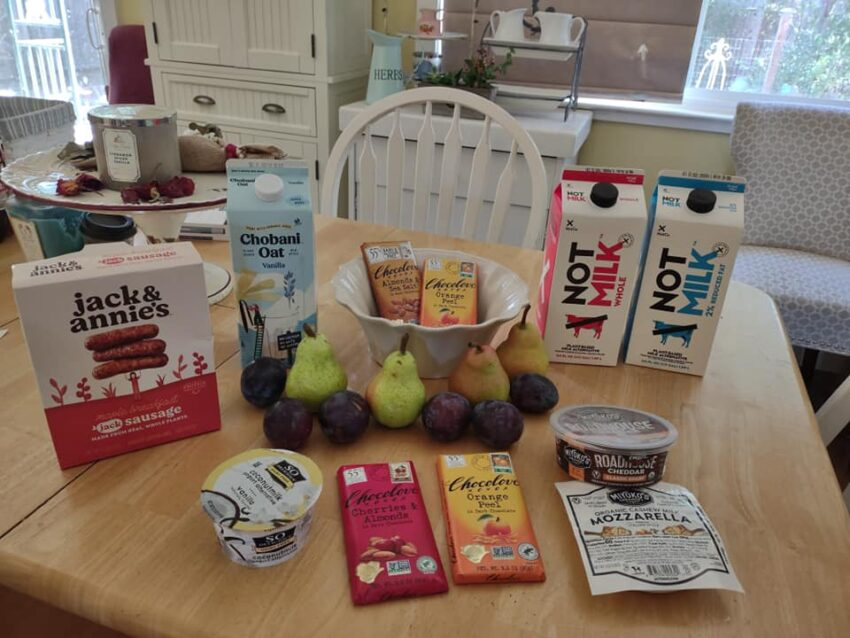 Sprouts shopping trip on my kitchen table: Not Milk, Chobani Oatmilk, Chocolove Bars, Miyoko's Cheeses, pears, plums, So Delicious yogurt